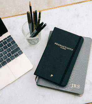 Jessica Sturdy's Chicago Office: Gold Apple Macbook laptop, white marble table with hammered gold legs, black productivity planner, monogrammed leather notebook