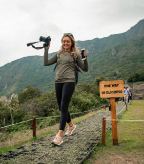 Jessica Sturdy of the travel blog Bows & Sequins at Machu Picchu in Peru on Remote Year Kahlo. Jessica is holding a Canon 5D Mark III camera and wearing a back pack, Lululemon long sleeve tee, black Lululemon leggings, and Adidas UltraBoost sneakers.