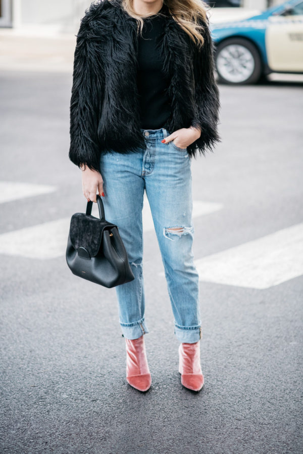 Fashion blogger Jessica Sturdy of Bows & Sequins wearing a faux fur coat, boyfriend jeans, and pink velvet booties.