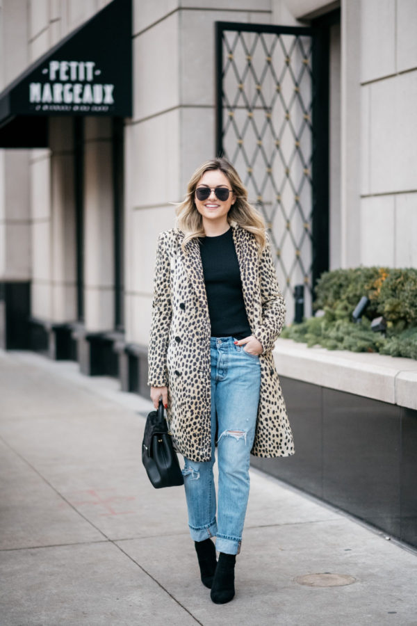 Chicago lifestyle influencer Jessica Sturdy of Bows & Sequins wearing a leopard coat with boyfriend jeans and black ankle booties.