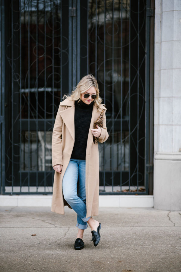 Chicago influencer Bows & Sequins wearing a long camel coat with a black turtleneck, boyfriend jeans, and black loafers.
