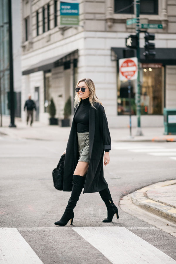 Chicago fashion blogger Jessica Sturdy of Bows & Sequins wearing a black turtleneck, suede skirt, black over the knee boots, and a long black duster coat.