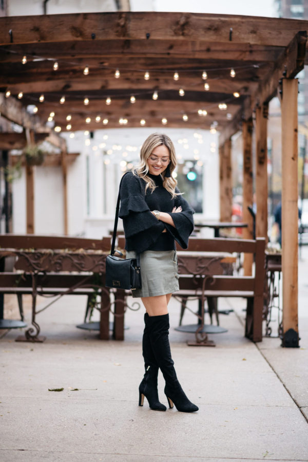 Chicago lifestyle influencer Jessica Sturdy of Bows & Sequins wearing a black ruffled sleeve sweater with a green suede skirt and black over the knee boots.