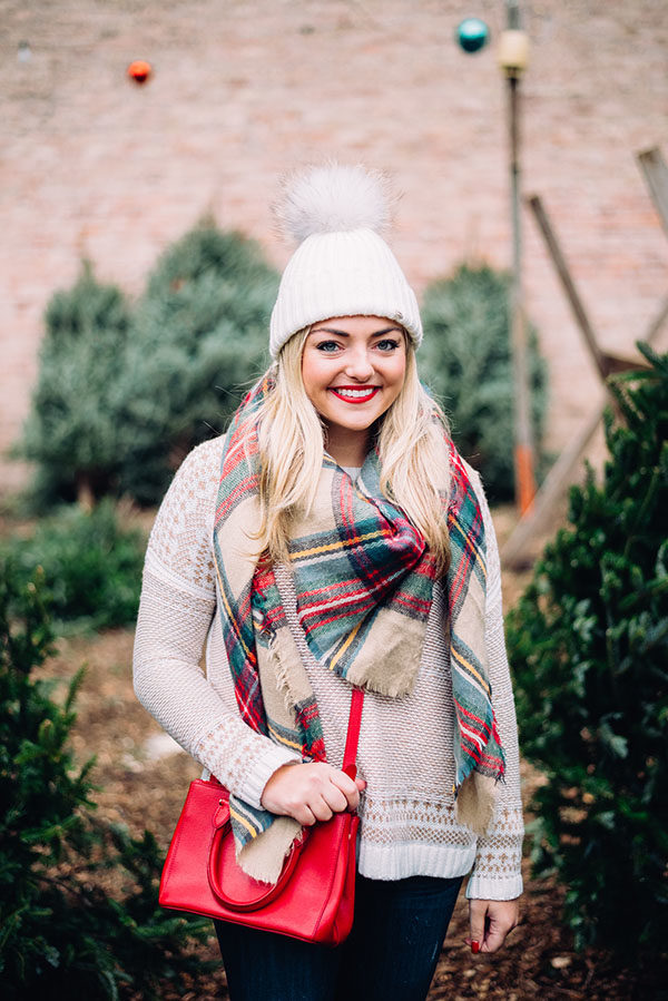 Chicago beauty blogger Jessica Sturdy of Bows & Sequins wearing a plaid blanket scarf with a fur pom pom hat at a tree farm.