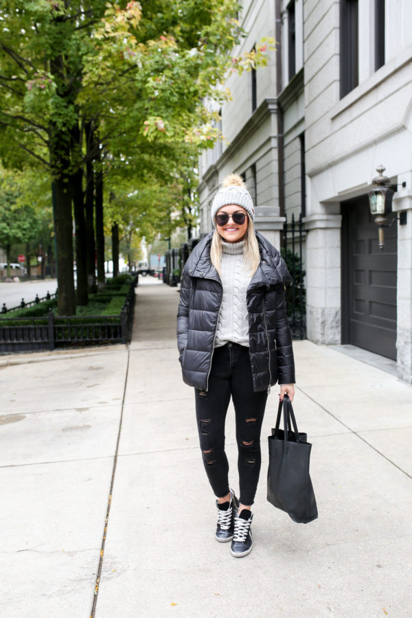 Health and fitness blogger Jessica Sturdy of Bows & Sequins wearing a black Barbour puffy coat with black jeans and sneakers.