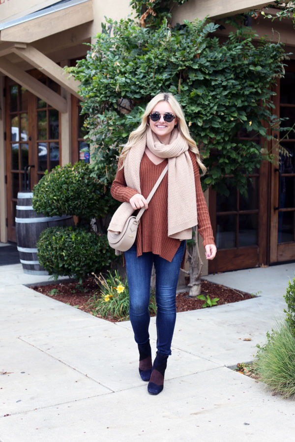 Fashion and travel blogger Jessica Sturdy of Bows & Sequins wearing an oversized cashmere scarf, skinny jeans, and booties for wine tasting in Napa.
