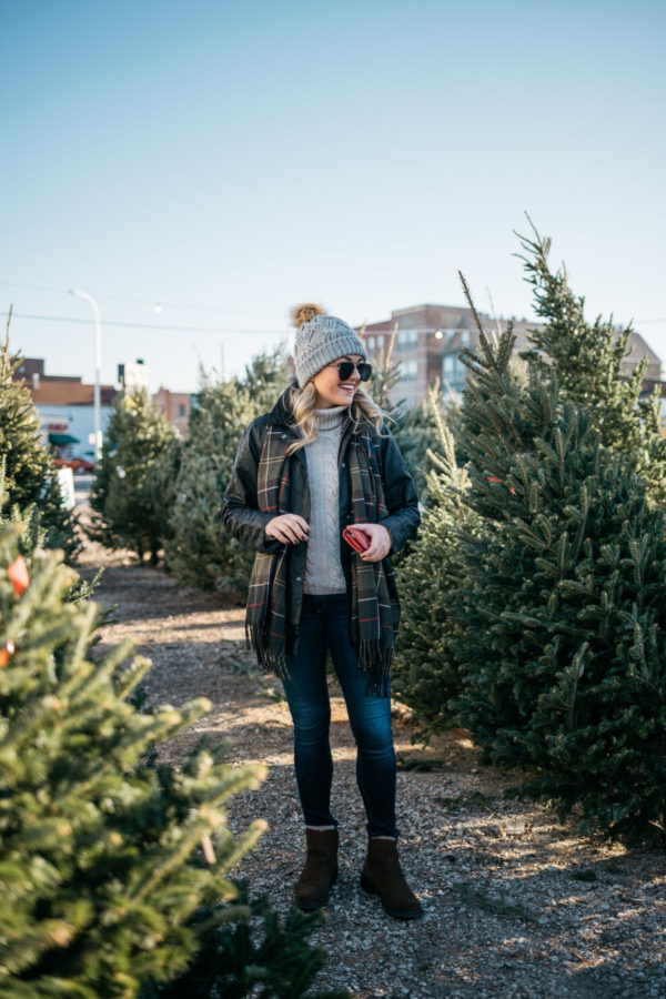 Chicago lifestyle blogger Jessica Sturdy of Bows & Sequins wearing a Barbour jacket, plaid scarf, and cable knit beanie at a tree farm in Chicago.