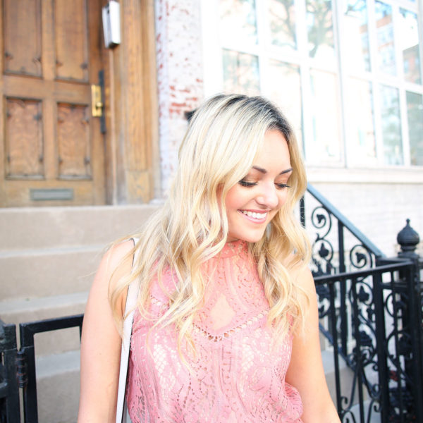 Jessica Sturdy with bright blonde hair wearing a pink lace dress during NYFW.