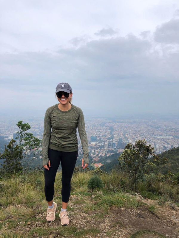 Jessica Sturdy is currently on Remote Year in Bogota, Colombia. She is wearing a blue Yankees baseball hat, black aviator sunglasses by Le Specs, lululemon leggings, and adidas Ultra Boost sneakers standing on the top of a mountain after a challenging hike overlooking the city.