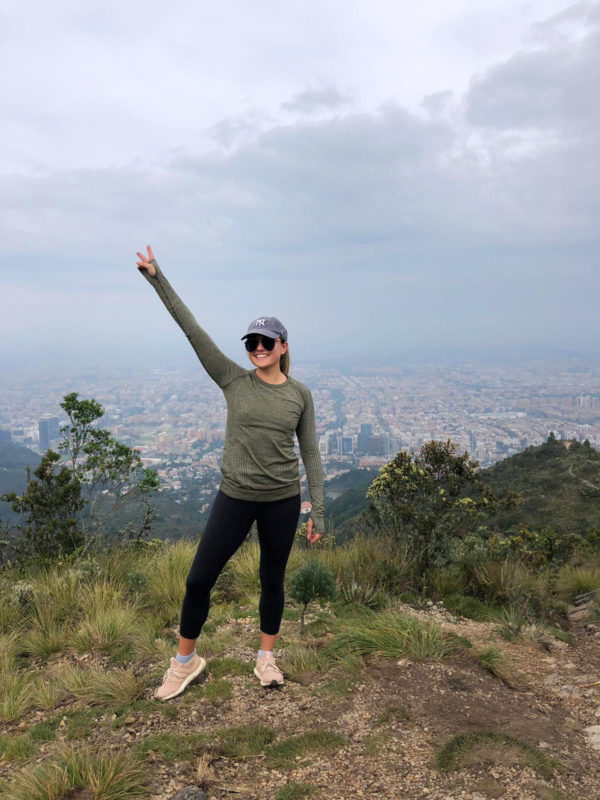 Travel blogger Jessica Sturdy in Bogota, Colombia on a morning hike. She's wearing a Yankees hat, black sunglasses, lululemon longsleeve and leggings, and adidas Ultra Boost gym shoes.