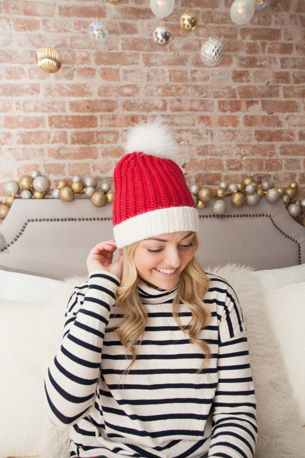 Bows & Sequins wearing a Kate Spade Santa Hat in her NYC apartment.