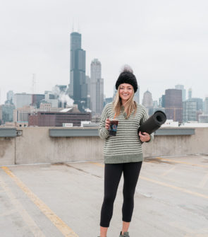 Fitness influencer Jessica Sturdy of Bows & Sequins wearing a mink beanie, American Eagle striped henley sweater, Lululemon leggings, and Adidas Flashback Sneakers with a Dunkin Donuts Energy Cold Brew and a yoga mat at the Core Power Yoga in the South Loop of Chicago with a view of the skyline and Willis Tower.