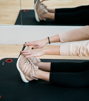 Chicago fitness influencer Jessica Sturdy shares her workout routine wearing Adidas UltraBoost sneakers, lululemon leggings, a Teletie, and an Ivy Park Cropped Sweatshirt stretching on a black yoga mat.