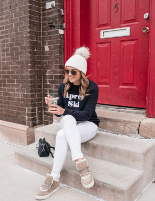 Chicago fashion blogger Jessica Sturdy of Bows & Sequins wearing an Apres Ski sweatshirt, white jeans, and shearling Marc Fisher sneakers with a white fur pom-pom beanie.