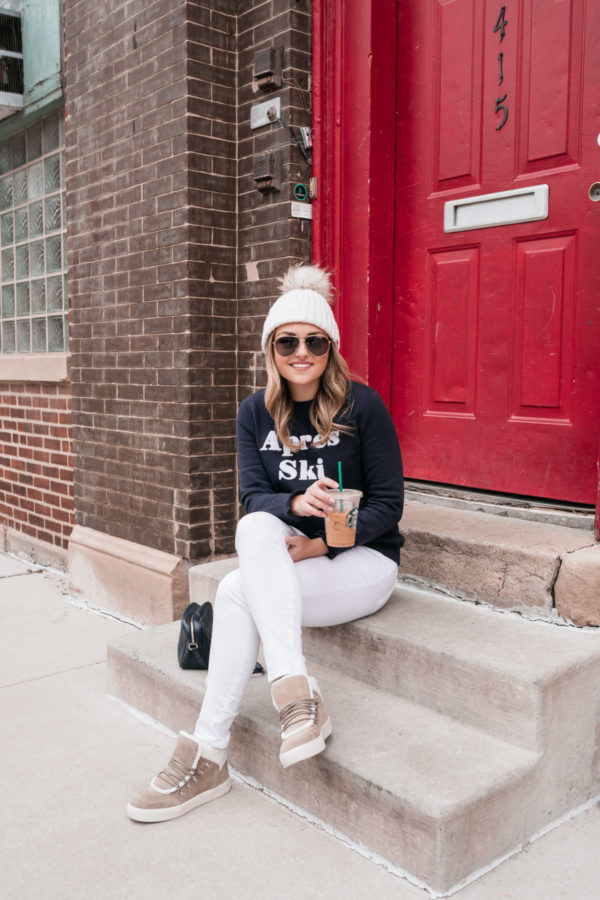 Travel and lifestyle influencer Jessica Sturdy wearing a pom-pom fur beanie, Gucci aviators, a navy blue sweatshirt, white jeans, and shearling sneakers sitting on a step in front of a red door in Chicago.