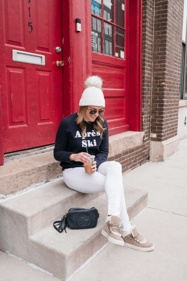 Chicago health and wellness influencer Jessica Sturdy sitting on a step in front of a red door wearing white jeans, shearling sneakers, and a pom-pom beanie.