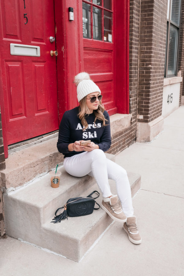 Chicago fashion and lifestyle influencer Jessica Sturdy wearing an Apres Ski sweatshirt with white jeans and shearling and suede sneakers.