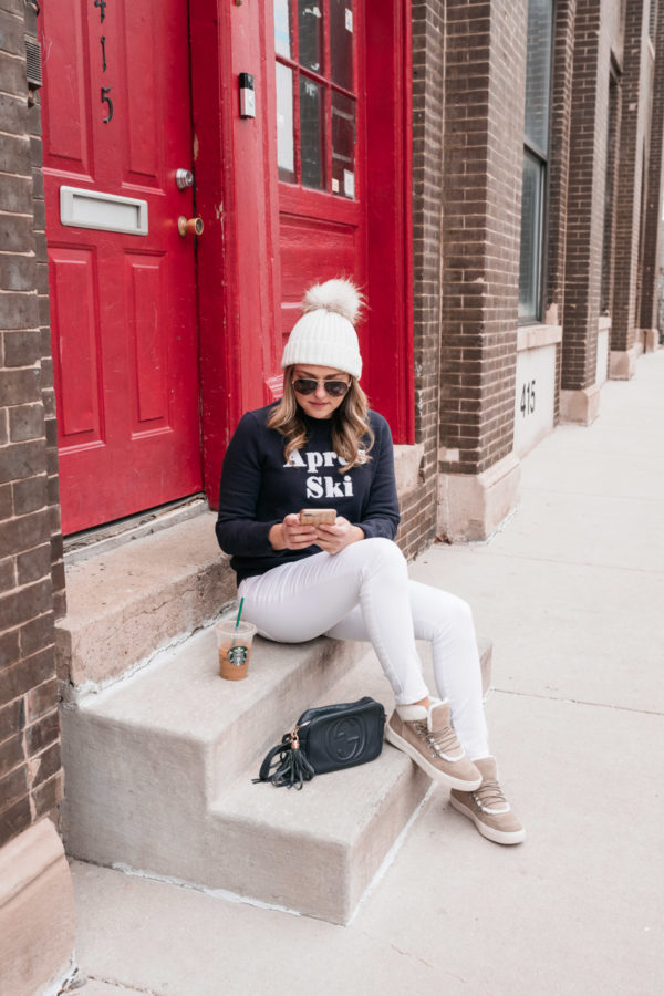 Chicago fashion and beauty blogger Jessica Sturdy wearing white jeans in the winter with a navy blue sweatshirt, a white fur pom-pom beanie, and shearling-lined suede sneakers.