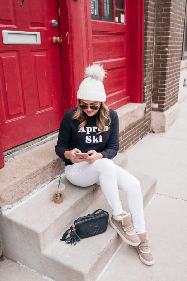 Jessica Sturdy, Chicago-based lifestyle and travel blogger, wearing a Nordstrom 1901 Apres Ski sweatshirt with white jeans while sitting on a stoop in front of a red door.