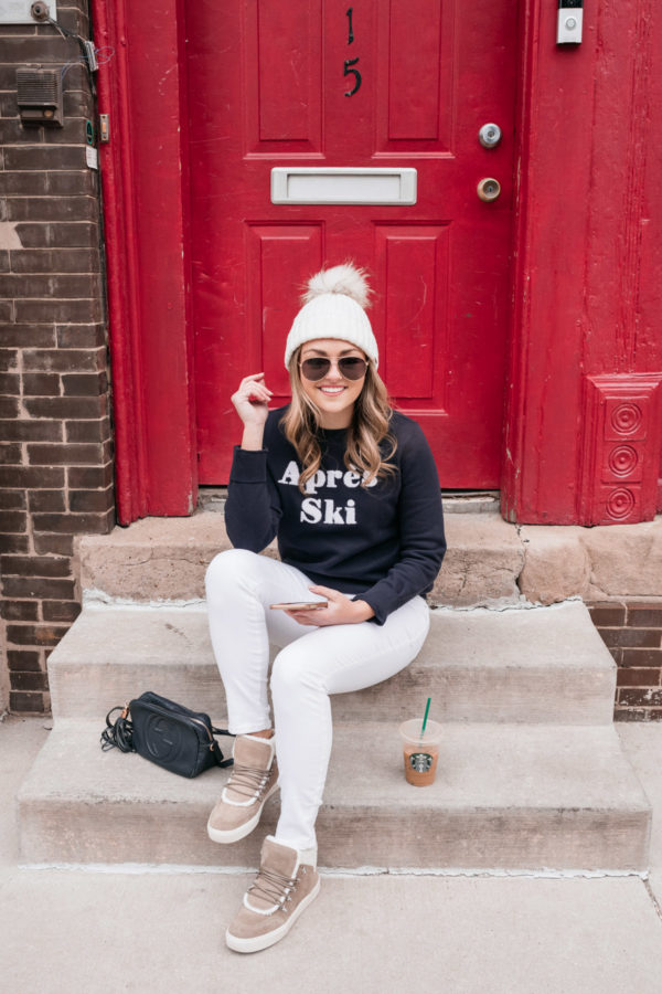 Everyday lifestyle blogger Jessica Sturdy sitting on a step in front of a red door in Chicago wearing a casual weekend outfit. She's styling a Yves Salomon beanie with Gucci aviators, an Apres Ski sweater, white jeans from Old Navy, a Gucci crossbody bag, and shearling-lined sneakers from Marc Fisher via Nordstrom.