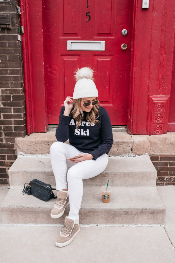 Health and wellness blogger Jessica Sturdy sitting on a stoop in front of a red door with an iced coffee and a cute winter weekend outfit.