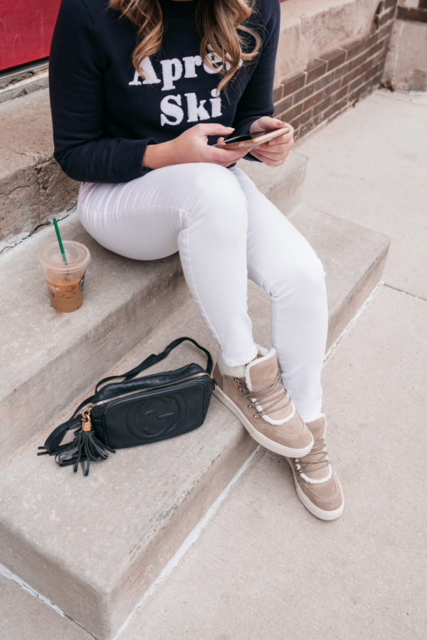 Approachable lifestyle blogger Jessica Sturdy mixes high and low with a casual weekend outfit wearing Old Navy white Rockstar jeans with a Gucci Soho Disco crossbody bag, a 1901 Nordstrom sweatshirt, and fuzzy sneakers from Marc Fisher.