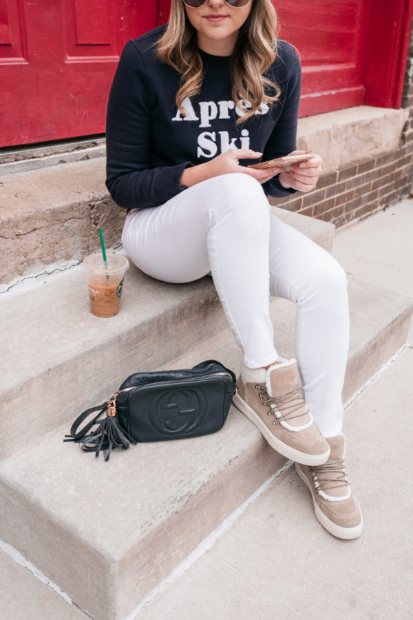 Chicago influencer Jessica Sturdy wearing white jeans, Marc Fisher Sana Sneakers, and a Gucci Soho Disco crossbody bag.