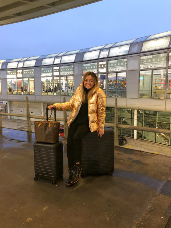 Chicago travel blogger wearing a rose gold puffer coat with black Away suitcases outside of Ohare International Airport.