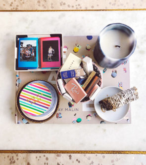 Jessica Sturdy styles the white marble coffee table in her Gold Coast apartment in Chicago. A blue and white candle, a white sage smudge stick, and colorfully striped Kate Spade Coasters are atop a Gray Malin Beaches book, along with a tray full of mini Fujifilm Instax polaroid pictures and a bowl full of matchbooks collected from her travels.