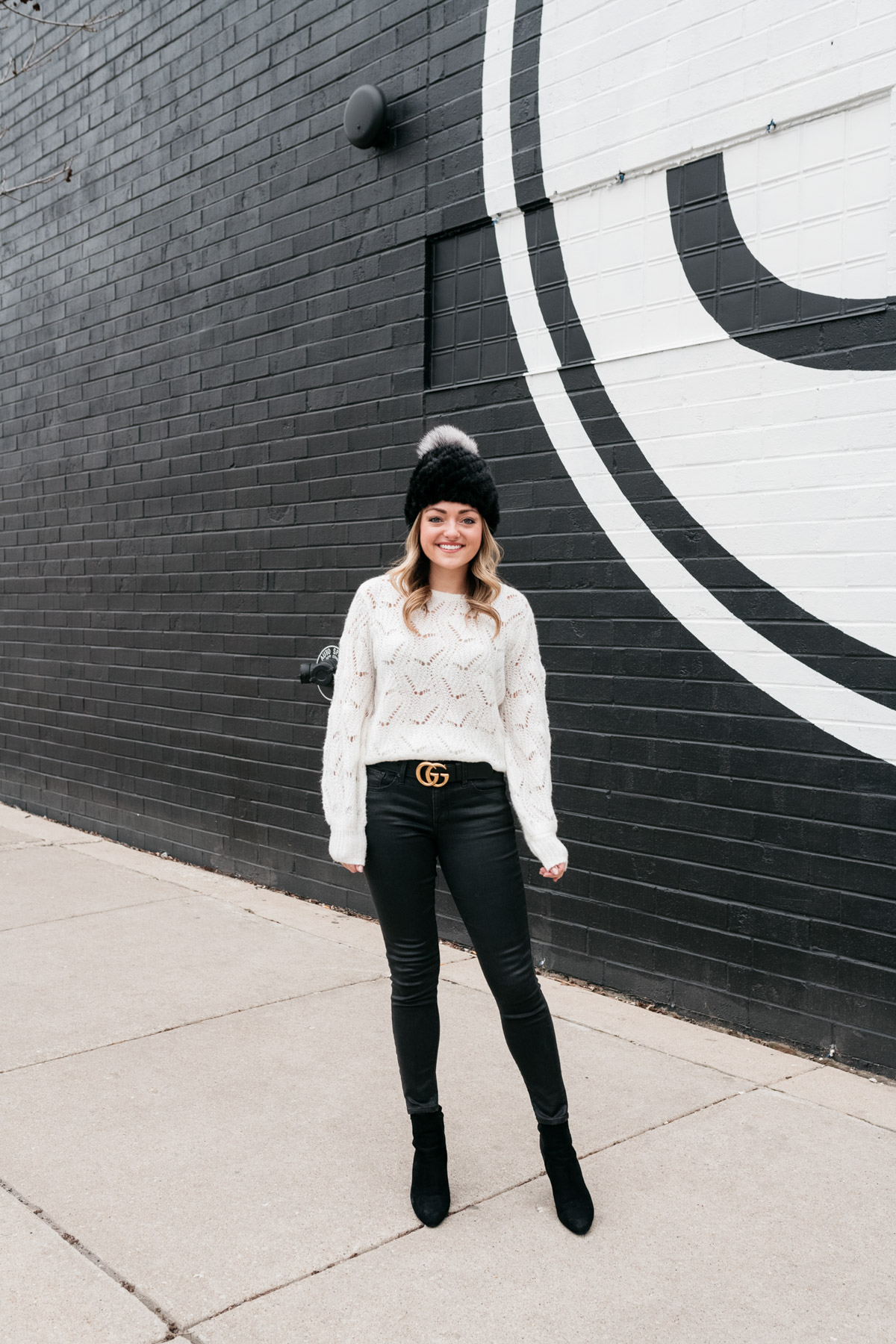 Chicago fashion blogger Jessica Sturdy wearing a fur beanie, Nordstrom sweater, a Gucci belt, coated black jeans, and heeled ankle booties.