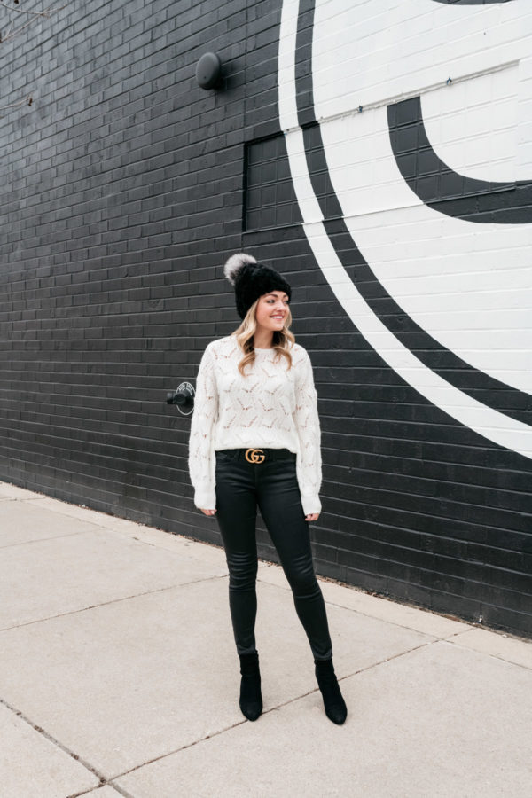 Chicago lifestyle influencer Jessica Sturdy wearing a fur beanie with a pom pom and a gucci belt.