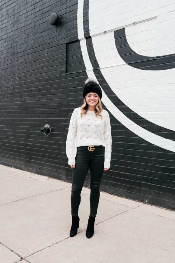Chicago-based blogger Jessica Sturdy wearing a monochromatic black and white outfit. She's styling a fur beanie with a pointelle balloon-sleeve sweater from Nordstrom, a Gucci belt, leather-like jeans, and black suede ankle booties.