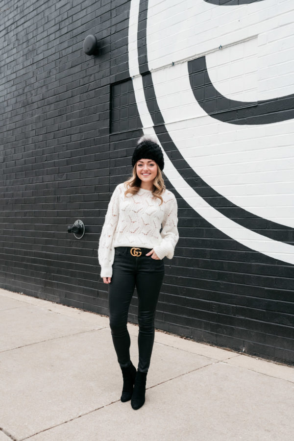 Chicago personal stylist Jessica Sturdy wearing a Kyi Kyi pom-pom beanie, a Nordstrom sweater, a Gucci belt, coated jeans from Express, and ankle boots for a cute winter outfit.