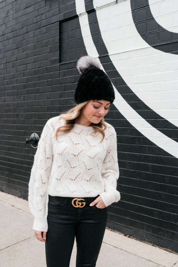 Chicago personal shopper Jessica Sturdy wearing a simple outfit that's elevated with stylish details like a fur beanie, textured sweater, coated jeans, and a logo belt buckle.