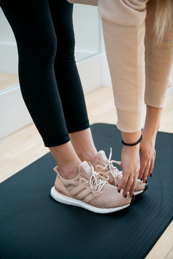 Chicago fitness blogger and Instagrammer Jessica Sturdy of Bows & Sequins wearing Adidas UltraBoost sneakers, black Lululemon leggings, a cropped blush pink Ivy Park sweatshirt, and a Teletie while stretching in a workout studio.