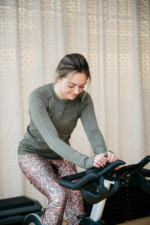 Chicago health and wellness blogger Jessica Sturdy wearing an olive green Lululemon long-sleeve tee with Terez glitter leggings on a stationary bike in a spin studio in Chicago.