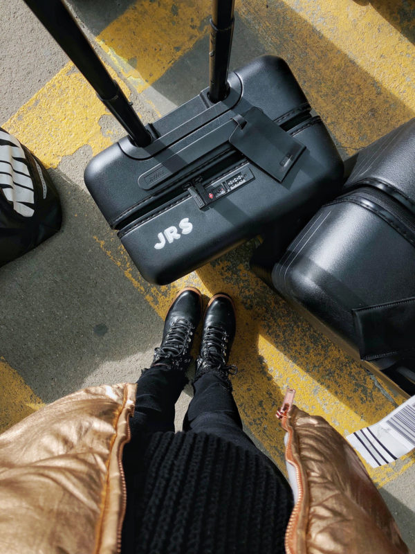 Chicago travel blogger wearing black leather boots with monogrammed black Away suitcases.