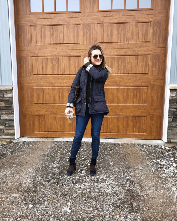 Real outfit blogger wearing a quilted navy blue Barbour jacket, skinny jeans, and patchwork booties.