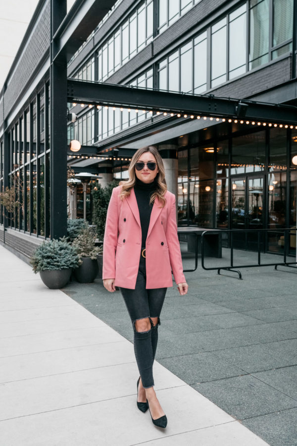 Jessica Sturdy of Bows & Sequins wearing a pink double-breasted blazer, black turtleneck, ripped One Teaspoon jeans, black pumps, and Le Specs matte black aviators.