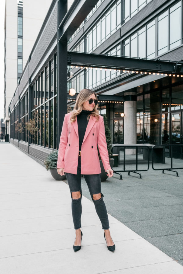 Chicago fashion influencer Jessica Sturdy styles a pink blazer from Nordstrom with a black J.Crew turtleneck bodysuit, One Teaspoon jeans, Kate Spade black pointed pumps, and a black and gold Gucci belt.