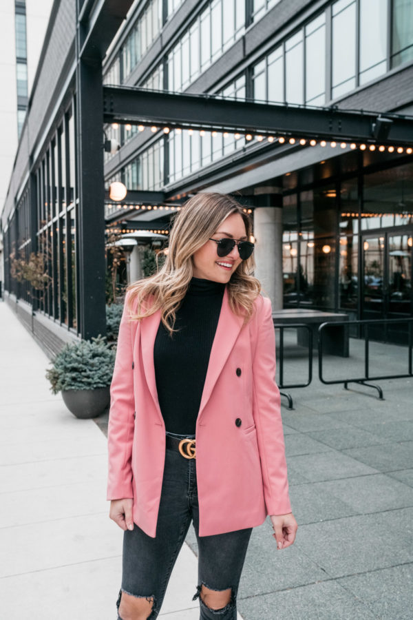 Chicago fashion blogger Jessica Sturdy styles a pink blazer with a black turtleneck bodysuit and Gucci belt in front of the Ace Hotel.