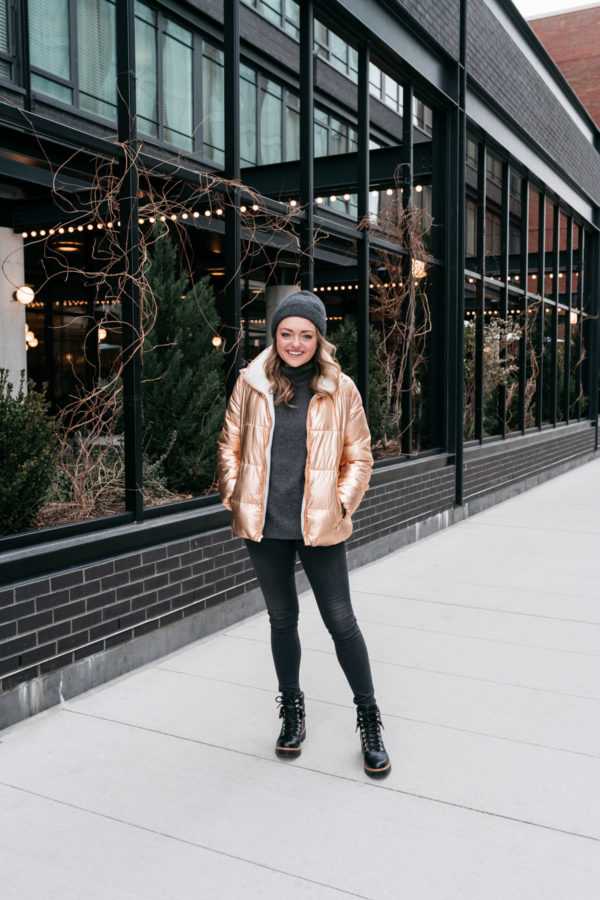 Midwest fashion and lifestyle blogger Jessica Sturdy styling a metallic rose gold jacket with a gray cashmere sweater and beanie, Rag & Bone skinny jeans, and Indigo Rd booties in front of the Ace Hotel in Chicago.