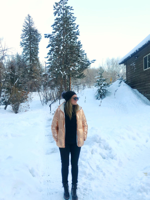 Chicago fashion blogger Jessica Sturdy wearing a rose gold puffer jacket with a black beanie, Le Specs Prince sunglasses, black jeans, and black leather boots in the snow in Colorado.