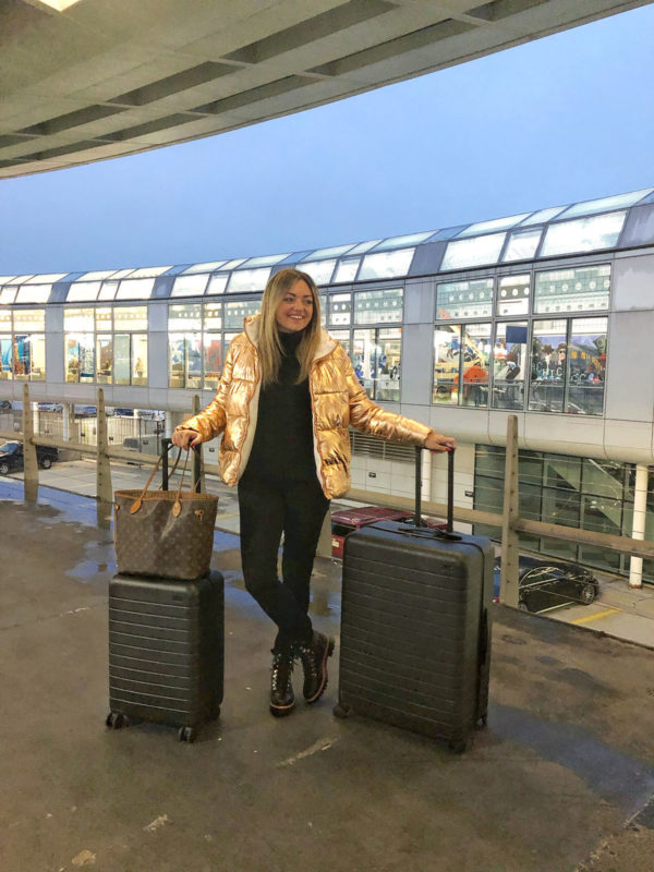 Fashion, travel, and lifestyle influencer Jessica Sturdy at ORD in Chicago wearing a rose gold puffer jacket with an Away Bigger Carry-On and an Away Large suitcase with a Louis Vuitton Neverfull bag.