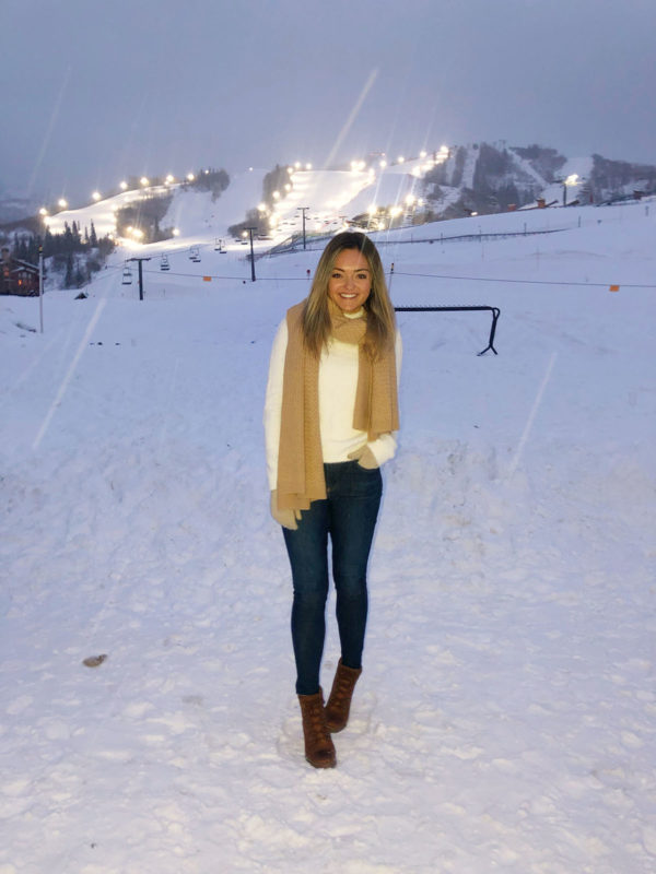 Fashion blogger Jessica Sturdy wearing a cashmere blanket scarf and white fuzzy turtleneck on the mountain for apres ski in Steamboat Springs, Colorado.