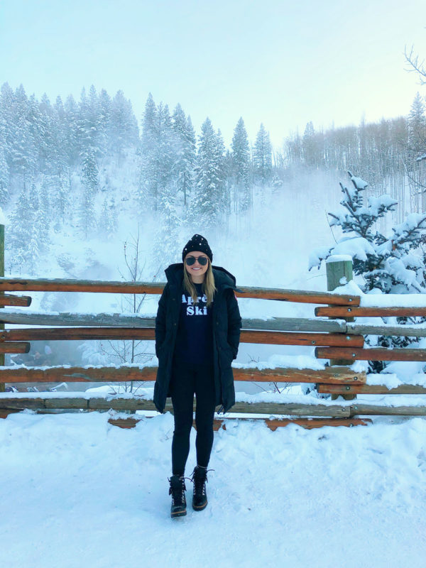 Fashion blogger Jessica Sturdy wearing an Apres Ski sweatshirt, a Canada Goose jacket, and a pearl beanie at Strawberry Park Hot Springs in Steamboat Springs, Colorado.