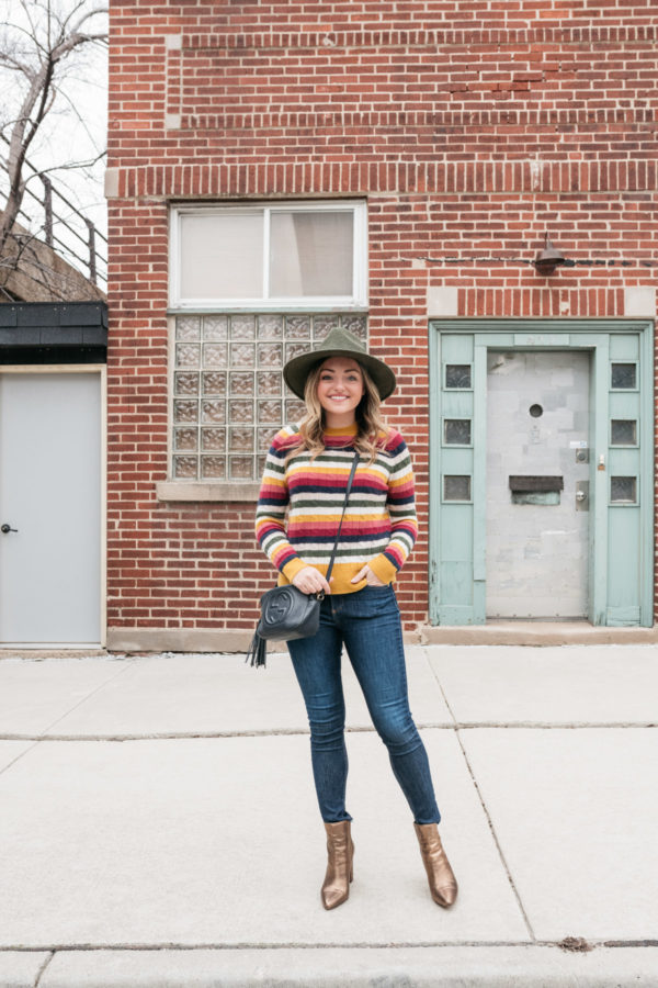 Fashion blogger Jessica Sturdy wearing a multi colored striped crewneck sweater with skinny jeans and ankle booties.
