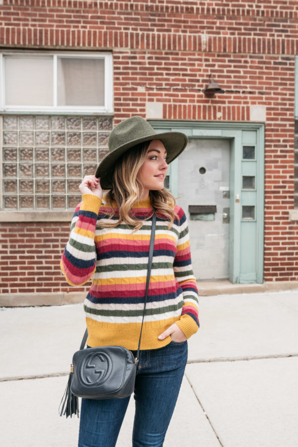 Chicago influencer Bows & Sequins wearing a wool hat by Barbour, a cashmere stripe colorful sweater, and a Gucci Soho Disco Bag in navy.