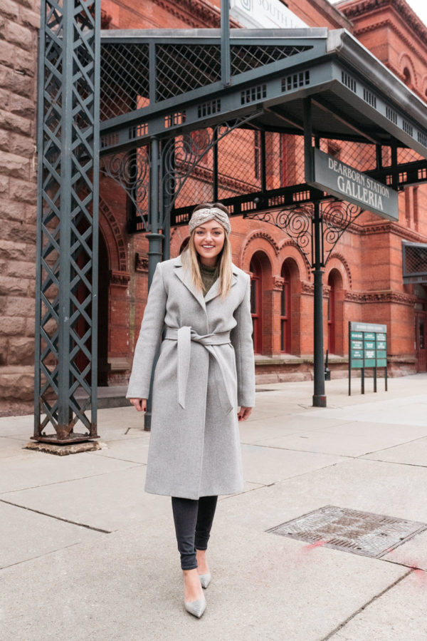 Chicago fashion influencer Jessica Sturdy wearing a long grey belted wool coat with d'orsay pumps and a sequins headband.