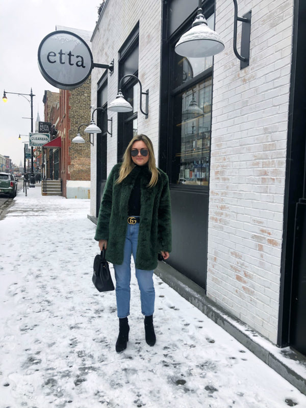 Bows & Sequins brunches at Etta in Chicago wearing a green faux fur coat, black turtleneck bodysuit, Gucci belt, mom jeans, and heels.